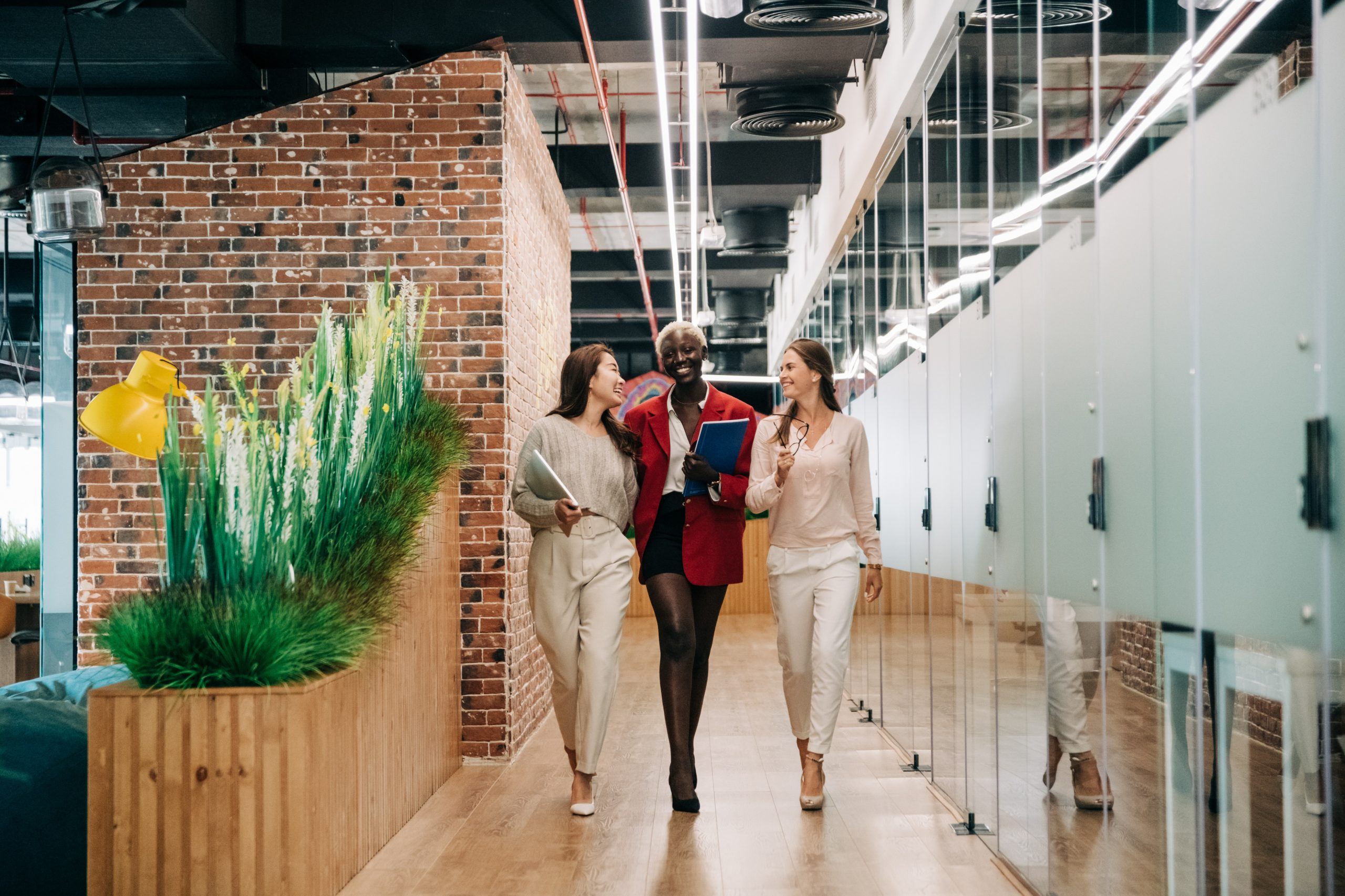 Three women executives are walking down the hallway in a modern office. They are talking and smiling happy to be back at work post pandemic..